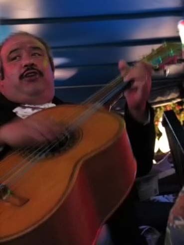 A mariachi strums his guitarrón mexicano at la Fogata in San Antonio, TX