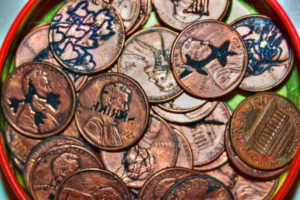 Tin of remaining etched pennies used in Margaret Craig's print project. There are 46 pennies left to be scattered. Will you be the next to find one?